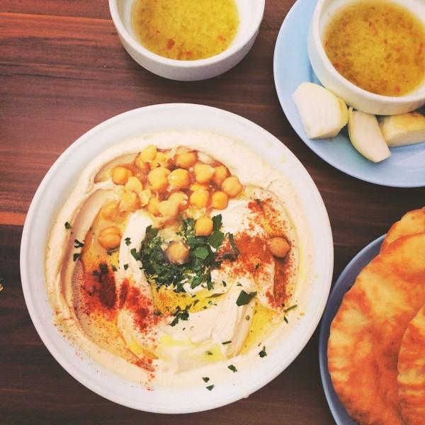 Hummus w Abu Hasan, podawany z chlebem pita, ostrą oliwą i cebulą do zagryzania