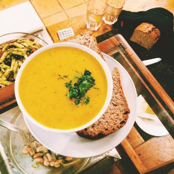 Zupa dnia z marchewki podawana z chlebem, a w tle sałatki z fasoli i makaronu