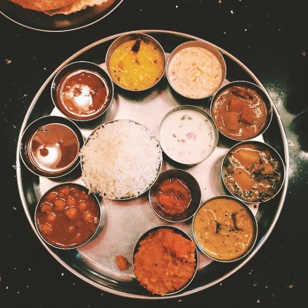 Południowo-indyjskie thali w wersji wegańskiej, w tle trzy ogromne, gorące chlebki
